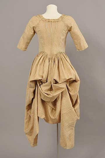 Cream silk robe a la anglaise retroussee, c. late 18th C. Cream silk with a striped design of tiny red and pink flowers, with closed bodice and overskirt in Irish polonaise style.