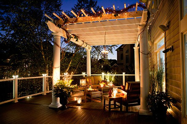 White pvc trellis at night with deck lighting and Trex Outdoor Furniture