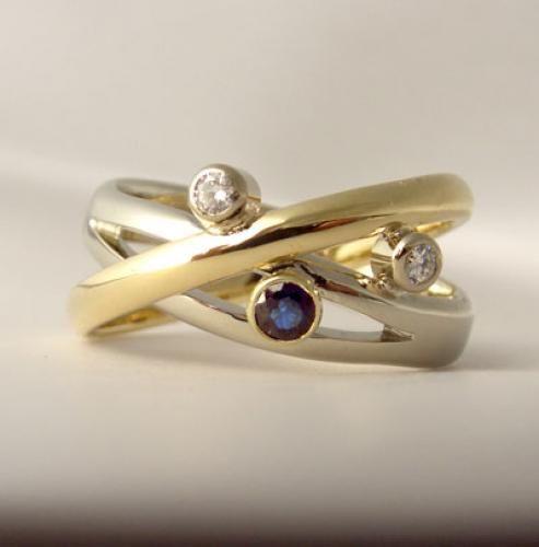 Witgouden ring waar een geelgouden ring overheen gemaakt is. Gezet met 2 diamanten en een blauwe saffier (blauwe saffier staat symbool voor huwelijkse trouw)