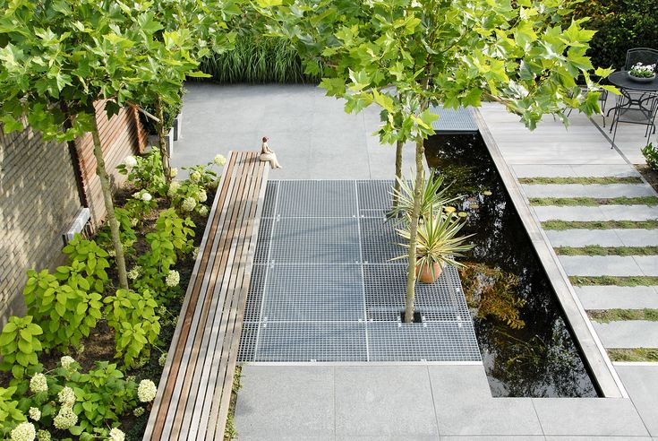 strakke moderne tuin met bordesroosters en dakplatanen.jpg