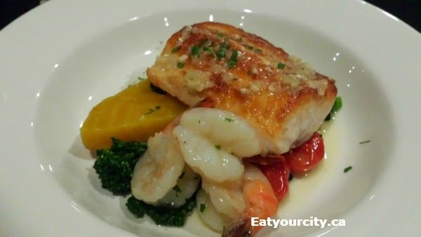 The Embarcadero Wine & Oyster Bar in Calgary, AB - Garlic butter pan seared salmon fillet, prawns, and vegetables
