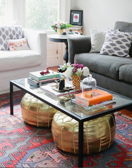 If you've got a coffee table with a low shelf, you might already have tucked some stylish or useful items under the main surface for storage. But don't neglect this spot for stuff if your coffee table is shelf-less! This little spot of floor space might be small, but it's not insubstantial. Here are some inspiring photos of folks using this space right!