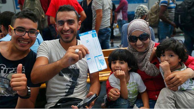 EinMann hält ein Bahnticket in die Kamera,sie dürfen aus Ungarn ausreisen