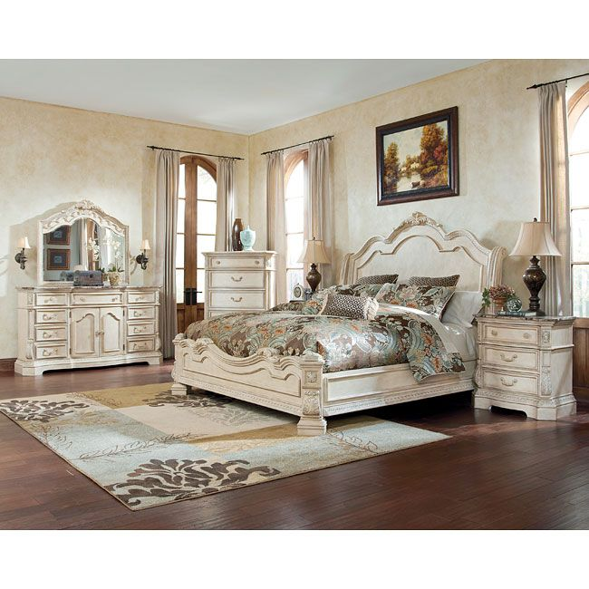 The exquisite Old World beauty of the Ortanique Sleigh Bedroom Set by  Millennium by Ashley Furniture comes to life with the opulent white finish  fl The exquisite Old World beauty of the Ortanique Sleigh Bedroom Set  . Ashley Furniture Sanibel Bedroom Set. Home Design Ideas