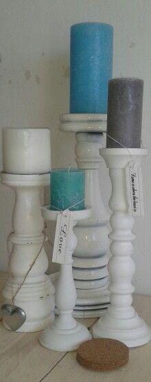 Verschillende soorten kandelaren met gekleurde kaarsen met houten hangers. #interieur #candles