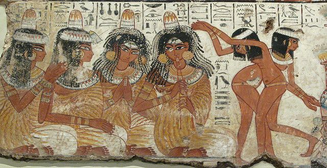 A painting of a feast for Nebamun to enjoy in the afterlife. Female musicians play pipes, clap and sign while young girls dance. They are singing 'The earth-god has caused his beauty to grow in everybody, the channels are filled with water anew, and the land is flooded with love of him.'  The ladies wear lumps of scented fat on their elaborate woolen wigs to help keep them cool. 1350 BC ..----British Museum