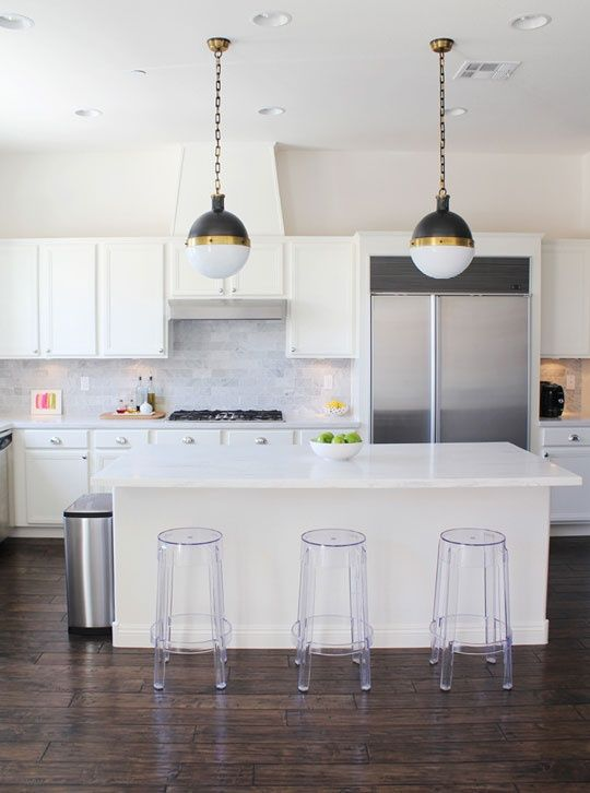 Stools: Lucite Ghost Stools, eBay  Flooring: Antico Vintage Distressed Plank Eco-friendly Engineered, Provenza  Tile: Carrara Marble Subway Tile (3x6), Home Depot  Countertop: Raincloud Countertops, Corian  Lighting: Thomas O'Brien Hicks Pendant Lamps, Circa Lighting