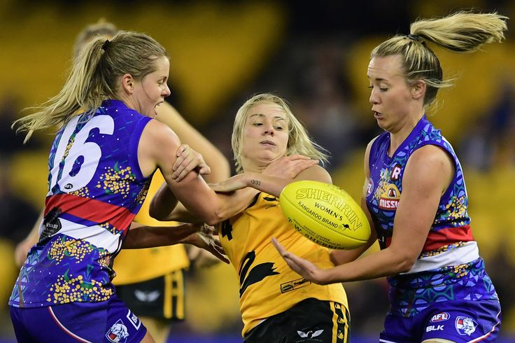 Demi Okely of Western Australia is tackled by Katie Brennan and Lauren Arnell of the Bulldogs during the Western Bulldogs v West Australia Women's Exhibition match before the round 11 AFL match between the Western Bulldogs and the West Coast Eagles at Etihad Stadium on June 5, 2016 in Melbourne, Australia.
