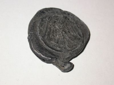 Lead cloth seal, stamped with the design of an eagle on one side and a bear with the letters 'S G' on the other, from St Gallen in Switzerland. This seal would have been attached to a bale of fustian (cloth made from linen and cotton). Lead seals were attached to bales of cloth for quality control. They provide details about the fabric: brand name, size and source, as well as the maker's personal mark. Production Date: Late Medieval; 15th century