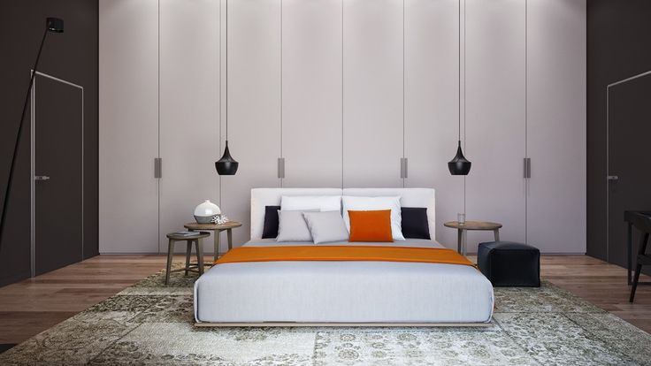 Light lines stream through in the bedroom space, simplistic in brown and white high-ceilinged walls. A fleur-de-lis Turkish rug ties the two together, while bursts of orange in the throw and cushion add a focal point to the room. Black hanging lights and desk features round out the feel.
