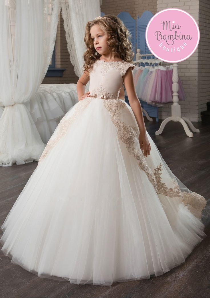 This Sacramento flower girl dress features a lace trimmed bateau neckline and a cap sleeved satin bodice that cascades into an illusion hi-low overskirt detail with a lacy border. The silhouette is co