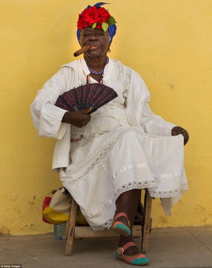Smoke break: A Cuban woman puffs on an enormous cigar as she fans herself on a street in Old Havana