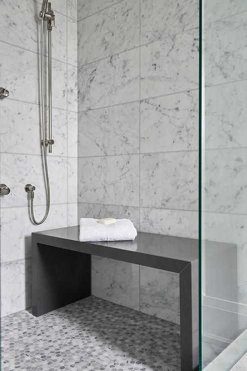 Contemporary bathroom shower is filled with white grid marble tiles lined with a freestanding gray quartz waterfall shower bench placed atop a gray hex shower floor.