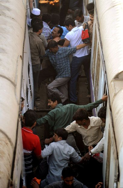 Commuters attempt to climb from one train to another during rush hour at a suburban railway station in Mumbai.