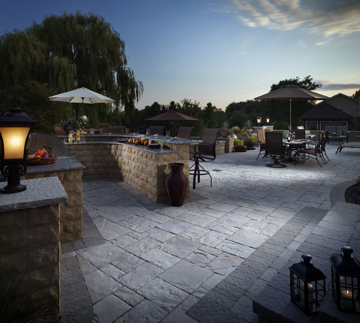 The perfect patio for entertaining! This outdoor living area features an outdoor kitchen with wrap-around bar seating and additional outdoor dining area. #MegaLafittPaver #BelAirWall