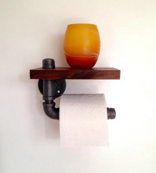 Old steel pipe and a strip of wood work together beautifully to create a rustic toilet paper holder that is sure to be the hit of your bathroom. | via diyncrafts.com