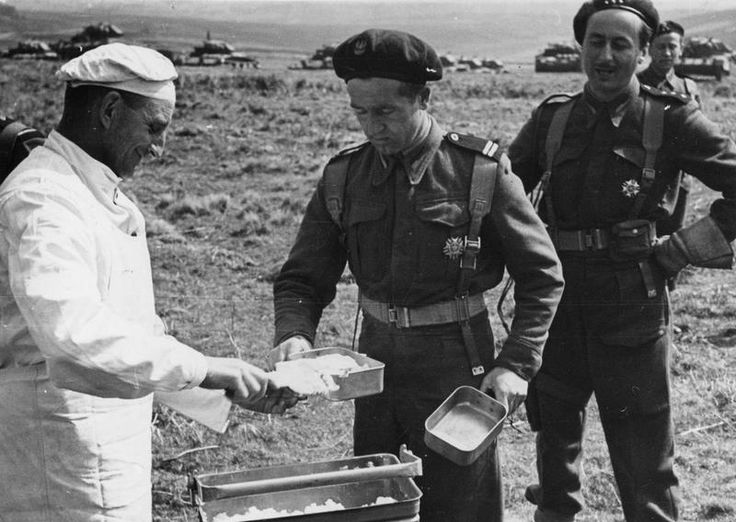 THE POLISH ARMY IN BRITAIN, 1940-1947 - Troops of the 1st Armoured Division receiving their hot rations during the field manoeuvres, 17 May 1943. Note a line of divisional Crusader tanks in the background.