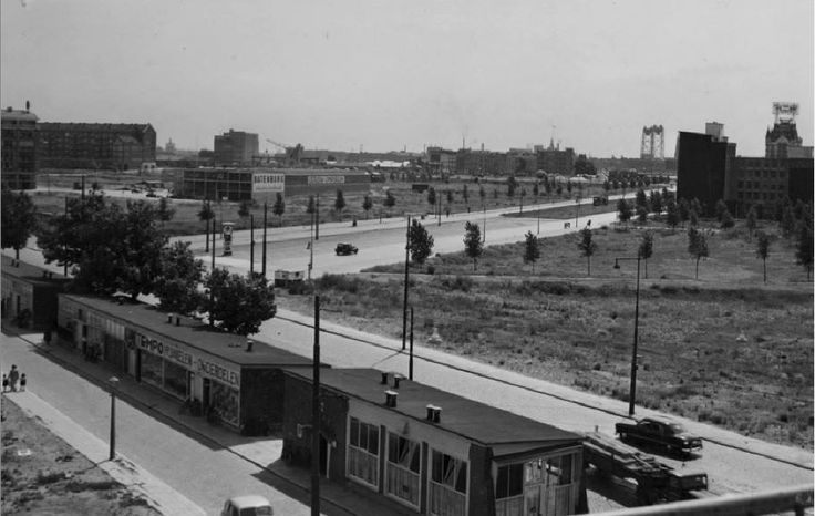 Gezicht op de nog vrijwel onbebouwde Mariniersweg met op de voorgrond de Goudsesingel met noodwinkels. Op de achtergrond zie je het Witte Huis en de Hef. De foto is gemaakt tussen 1950 en 1954. De Mariniersweg herinnert aan het heldhaftig optreden van de mariniers in de meidagen van 1940.