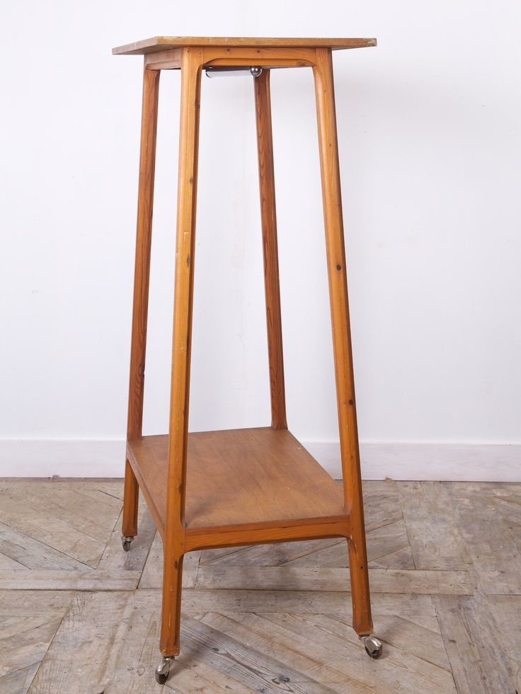A tall freestanding retail display unit. Splayed leg Maple frame with pine shelves supported on original steel castor, deep stop chamfering to the legs. English 1930s