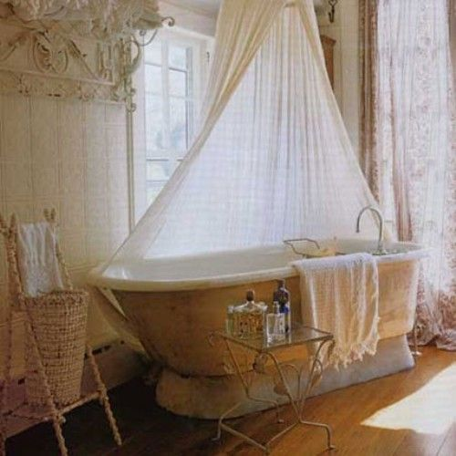 The New Home Decor - Shabby chic style creates a romantic feeling in this bathroom.  Love the canopy above the tub that creates privacy from the window.  Gorgeous linens add luxury to bathroom designs.