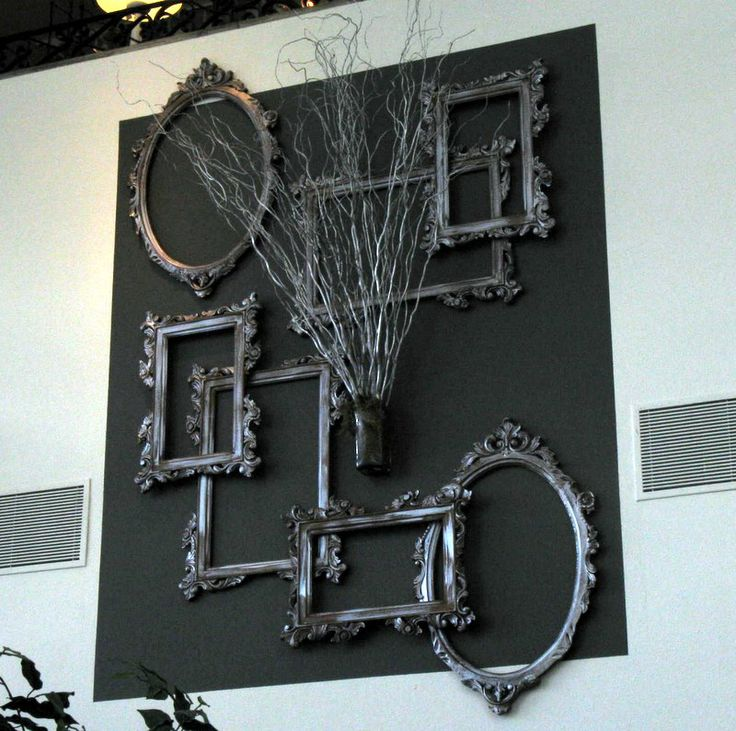 I like the basic idea, minus, the black background and twigs - display of silver painted frames on the large wall space