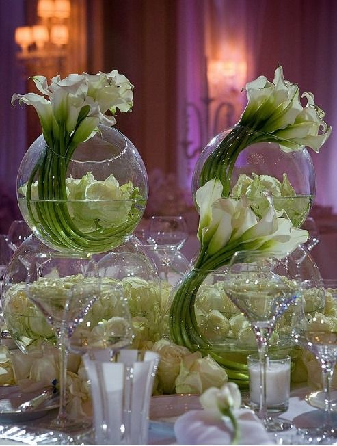White calla lilies curled into circular glass vases make a striking and appealing centerpiece for any reception table.