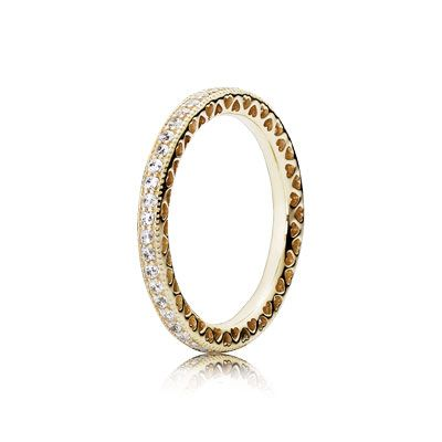 Elegantly designed, this refined 14k gold eternity ring is an indispensable part of your jewelry collection. Wear it alone to draw attention to the dainty cut-out heart pattern or add it to a ring stack as a luxurious stacking piece. #PANDORA #PANDORAring