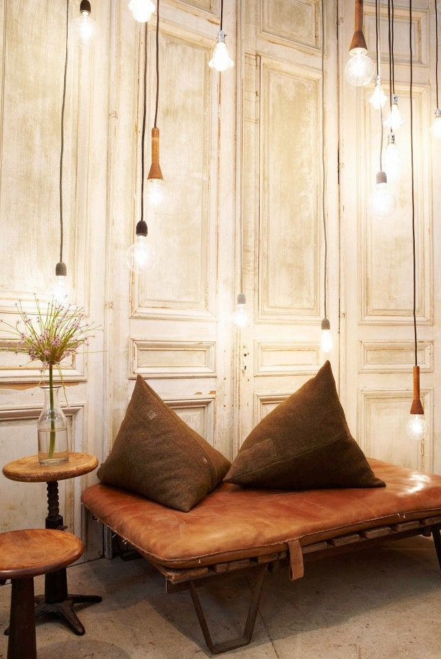 Bare bulbs over a leather daybed with paneling