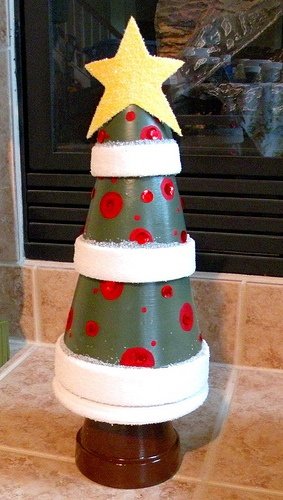 """Such a cute idea! It's a 3"""", two 4"""", and a 6"""" flower pot stacked upside down on top of a 6"""" flower pot saucer to make a Christmas tree. I wish I would have thought of this about 7 years ago for a 4-H project!"""