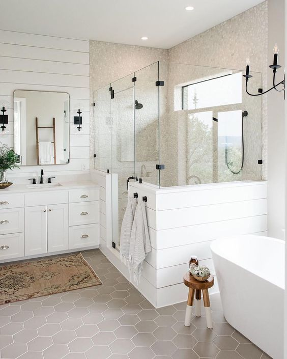 A White Farmhouse Bathroom With Plank Walls Grey Hex Tiles An Oval Tub A Vintage Vanity And