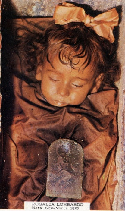 .This is one of the best-preserved bodies in the world. Her name is Rosalia Lombardo, her eyes are slightly open, and she's a Sicilian two-year-old who died of pneumonia in 1920. Her body was embalmed and placed in the Capuchin catacombs of Palermo.    National Geographic reports that the special formula used to embalm her has finally been decoded. You can also watch a video of researchers examining her body.