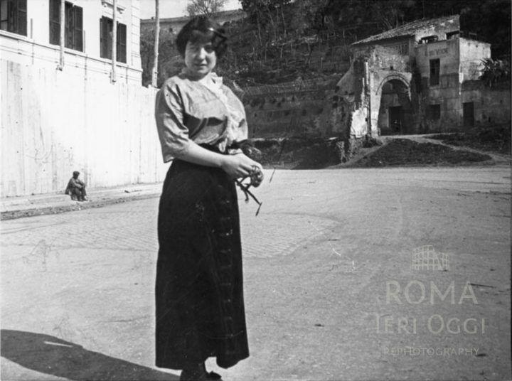 Via Giovanni Branca (1915)  Giovane donna fotografata in mezzo alla strada, alle sue spalle l'Arco di San Lazzaro su Via Marmorata.