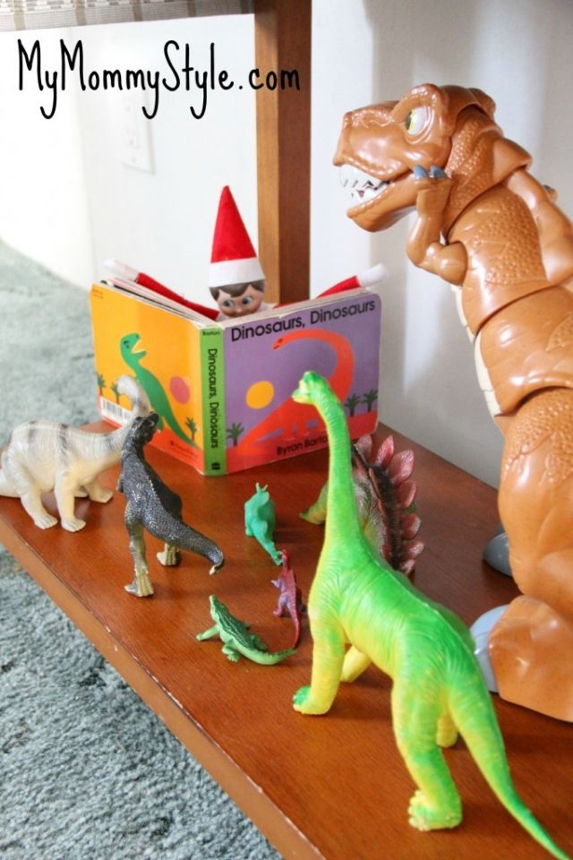 Elf on the Shelf, reading a Dinosaur book to all the Dinosaurs....