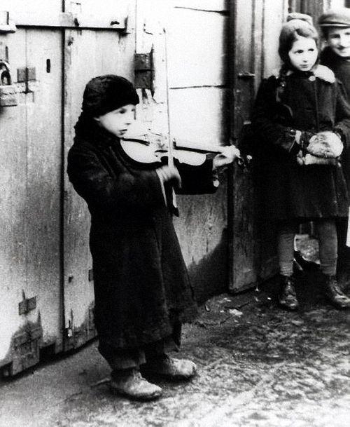 Un niño judío que toca un violín para sobrevivir en el gueto de Varsovia, Polonia, febrero 1941.