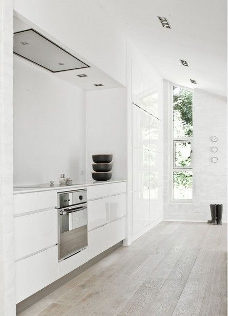 High gloss cabinets & hickory floors; wall of tall cabinets; natural light; white walls