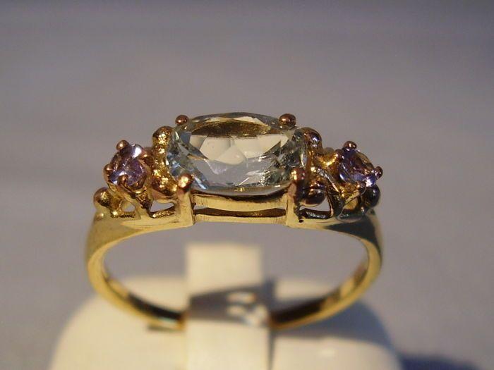 Rose gouden ring met geteste Aquamarijn (1.2 ct) en twee tanzanites (03 ct in totaal)  De ring is gemaakt van 333 = 8 kt rose goud en gestempelde dienovereenkomstig op de ring band.Het hoofd van de ring wordt ingesteld met een ovale gefacetteerde geteste en echte Aquamarijn met zeer mooie intense kleur en zeer goede schittering. Het heeft 1.20 ct. Dit wordt geflankeerd aan beide zijden bekleed met ronde gefacetteerde tanzanites van 030 ct in totaal.Maat 57 = 181 mm ring band…