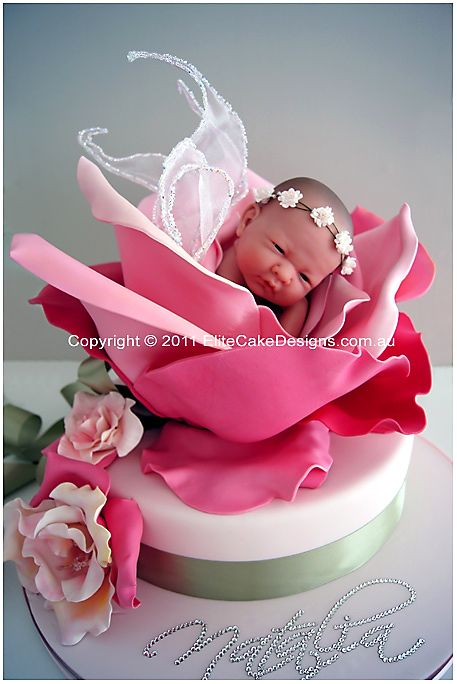"""Natalia"" Baby Fairy Rose  Christening Cake  Our exclusive signature series Christening Cake Design featuring a baby fairy with Swarovski crystal-outlined wings, inside a fully sugarcrafted rose.  Child's name is beautifully designed on the board in Swarovski crystal diamantes.  Servings 142 coffee or 57 dessert  Price $4,650 Lead time required: 16 weeks"
