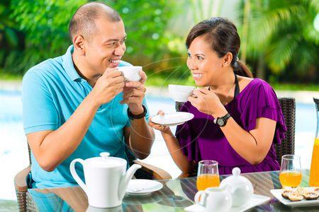 foto de Pares asiáticos que comem o café no patamar casa