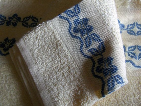 Pair of terry towels, cotton cream.  They have a band at the bottom of the Aida fabric on which were embroidered cross-stitch borders of flowers.