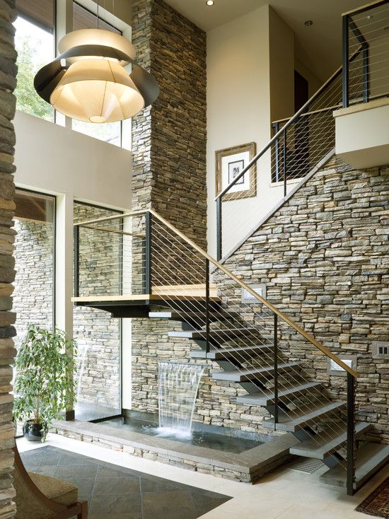 A breathtaking water feature flows below the staircase, designed by Alan Mascord Design Associates Inc