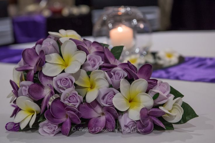 "Wedding photographer, Candid Photos of a Lifetime  The beautiful ""cadbury chocolate"" puple bouquet with white & yellow frangapani flowers...  with the wedding rings & candle in the background"