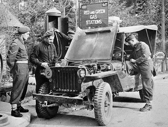 """Personnel of the Loyal Edmonton Regiment filling a jeep with gasoline, San Lorenzo in Monte, Italy, ca. 22 September 1944. The vehicle is marked with the formation sign of I Canadian Corps and bears a Class 2 bridging disc. """"Essantee"""" was a name applied to the Army's service stations - red and green were the Arm of Service colours of the Royal Canadian Army Service Corps. LAC photo."""