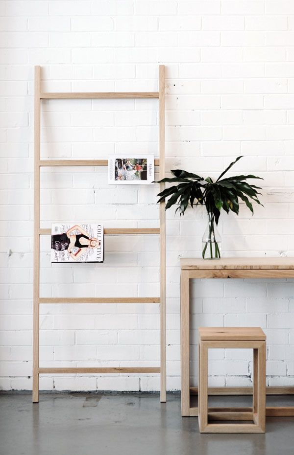 Polished concrete floor, exposed brick wall painted white, wooden table, stool, magazine rack ladder