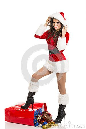 Beautiful smiling girl in Santa Claus costume posing with one leg on big red shopping bag full of Christmas presents.
