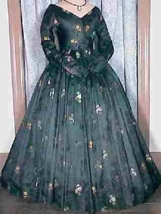 1850s brocaded silk dress A glorious circa 1850s ladys black silk brocade dinner or evening gown with a bold floral motif of gold, ivory, red, pink and yellow flowers, some roses, with green sprigs, that make for a striking contrast against a floral and honeycomb patterned background. It has a V-shaped construction to the front and back of the bodice with a deep point to the front. It closes with a back hook and cloth eye closure. It has long slender fitted sleeves with capp