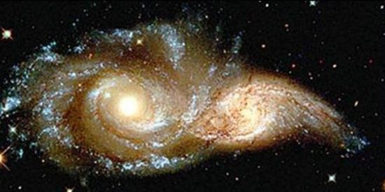 Hubble picture - The glowering eyes from 114 million light years away are the swirling cores of two merging galaxies called NGC 2207 and IC 2163 in the distant Canis Major constellation.
