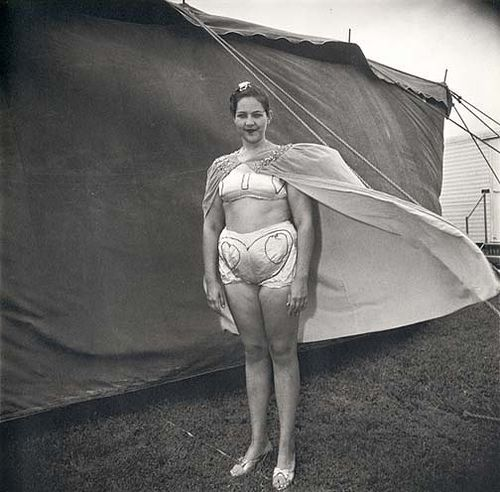 Girl in her circus costume, MD, 1970    By:  Diane Arbus.     This is the art of diane arbus: capturing the essence of the people she photographed; here this woman in a marginal occupation, in a costume otherwise ridiculous, expresses grace, dignity  and good nature.