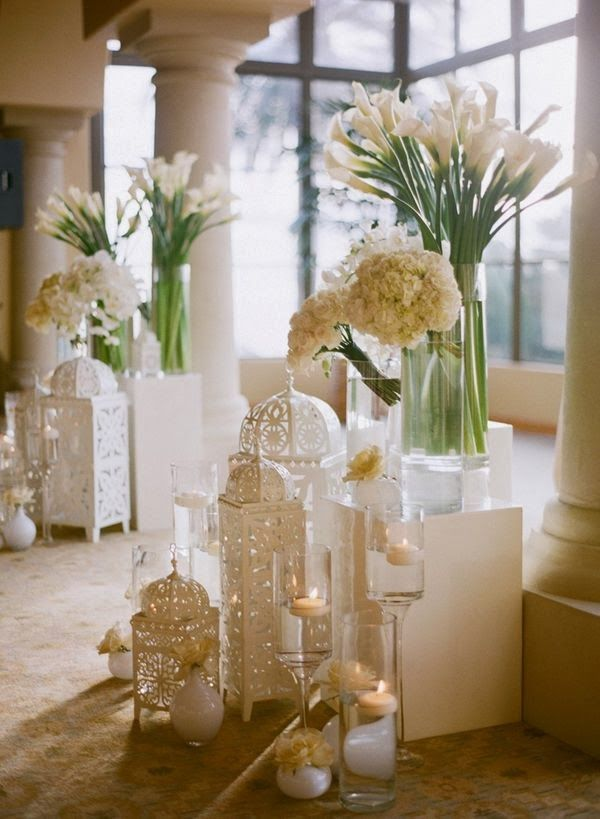 A great way to decorate a cocktail area using levels, floral arrangements, and beautiful lighting.