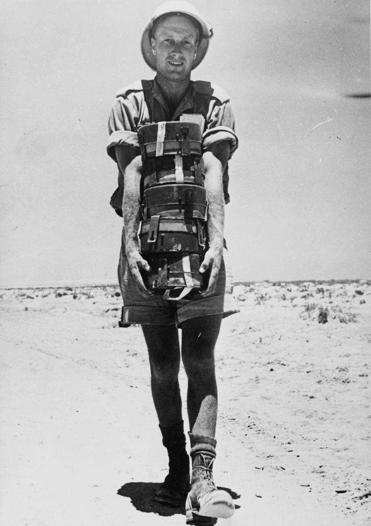 Western Desert: This South African sapper is carrying a load of death -- German anti-tank mines Mk.IV. Sappers were a little less concerned when dealing with the big boy busters -- they wouldn't explode if a human stepped on them.