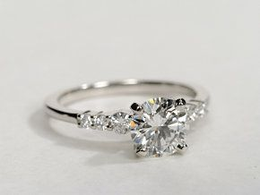 Capture your lasting love with this delicate platinum engagement ring, showcasing pavé-set round diamonds along the shank and your choice of center diamond.